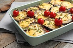 Beringela cozida com tomates e queijo no dishware na tabela de madeira fotos de stock royalty free