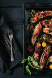 A beringela e os vegetais cozidos em uma bandeja e em um vintage pretos do metal bifurcam-se em um fundo preto do espaço da obscu imagens de stock royalty free