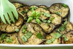 Beringela fritada e cozinhada com manjericão do alho no azeite fotografia de stock