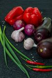 Beringelas frescas, pimenta, alho, cebola no fundo preto foto de stock