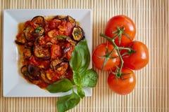 Beringelas no molho de tomate com tomates frescos Fotografia de Stock Royalty Free