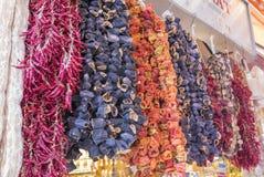 Beringelas secadas, pimentas e outros vegetais pendurando em cordas no bazar em Istambul, fotografia de stock