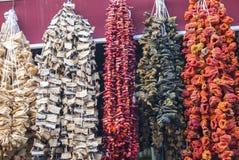 Beringelas secadas, pimentas e outros vegetais pendurando em cordas no bazar em Istambul, imagem de stock royalty free