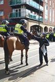 Berittener Polizist empfängt Wasser Stockfotografie