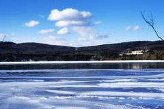 The berkshires in stockbridge massachusetts. A frozen lake in the berkshires in stockbridge massachusetts on a sunny blue sky winter day royalty free stock image