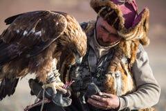 Berkutchi - chasseur kazakh avec l'aigle d'or, tout en chassant aux lièvres en montagne de désert de la Mongolie occidentale images libres de droits