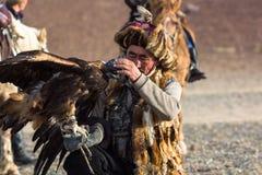 Berkutchi - chasseur kazakh avec l'aigle d'or, tout en chassant aux li?vres en montagne de d?sert de la Mongolie occidentale photo libre de droits
