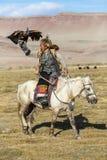 Berkutchi Eagle Hunter auf dem Pferd bei der Jagd zu den Hasen mit von Steinadlern auf seinen Armen Lizenzfreies Stockfoto
