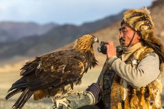 Berkutchi Eagle Hunter bei der Jagd zu den Hasen mit von Steinadlern auf seinen Armen Lizenzfreies Stockbild