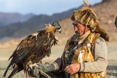 Berkutchi Eagle Hunter bei der Jagd zu den Hasen mit von Steinadlern auf seinen Armen in den Bergen von Bayan-Olgiiaimag Stockbild