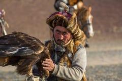Berkutchi Eagle Hunter bei der Jagd zu den Hasen mit von Steinadlern auf seinen Armen in den Bergen von Bayan-Olgiiaimag Lizenzfreie Stockbilder