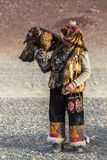 Berkutchi Eagle Hunter with golden eagle during hare hunting, in desert mountains of Western Mongolia. SAGSAY, MONGOLIA - SEP 28, 2017: Berkutchi Eagle Hunter Royalty Free Stock Photography