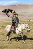 Berkutchi Eagle Hunter on the horse while hunting to the hare with a golden eagles on his arms Royalty Free Stock Photo