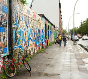 BERLÍN/ALEMANIA - CIRCA septiembre de 2012 - una bicicleta se ata contra un polo al lado de una pared llenada de la pintada Fotos de archivo