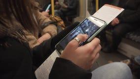 BERLÍN, ALEMANIA - 22 DE NOVIEMBRE DE 2018: Una muchacha mira las fotos en su smartphone, mientras que en el subterráneo almacen de metraje de vídeo
