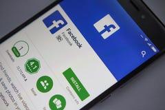 Berlín, Alemania - 19 de noviembre de 2017: Uso de Facebook en la pantalla del primer moderno del smartphone imágenes de archivo libres de regalías
