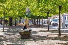 BERLÍN, ALEMANIA - JULIO 14,2018: Mujer joven desconocida que se sienta en el banco de piedra en parque de la ciudad en el día so fotografía de archivo libre de regalías