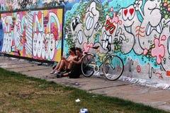 Berlín, Alemania, 2014: Un individuo y una muchacha se están sentando cerca de la pared con la pintada fotografía de archivo