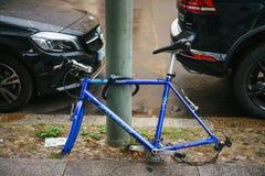 Berlín, el 2 de octubre de 2017: La bicicleta azul atada al pilar de la calle con la cerradura se coloca sin las ruedas después d Foto de archivo