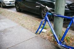 Berlín, el 2 de octubre de 2017: La bicicleta azul atada al pilar de la calle con la cerradura se coloca sin las ruedas después d Fotos de archivo