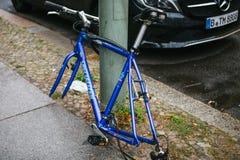 Berlín, el 2 de octubre de 2017: La bicicleta azul atada al pilar de la calle con la cerradura se coloca sin las ruedas después d Imágenes de archivo libres de regalías