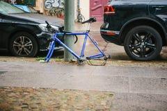 Berlín, el 2 de octubre de 2017: La bicicleta azul atada al pilar de la calle con la cerradura se coloca sin las ruedas después d Fotos de archivo libres de regalías