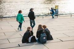 Berlín, el 3 de octubre de 2017: Un grupo de amigos de chicas jóvenes de los estudiantes que se sientan en la costa que está situ Imagenes de archivo