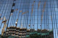 berl?n 06/14/2008 Fachada de cristal de un edificio con la reflexión de un emplazamiento de la obra Gr?as y andamio imagen de archivo