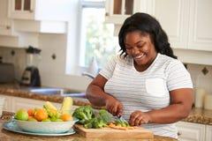 Überladene Frau, die Gemüse in der Küche vorbereitet Lizenzfreies Stockbild
