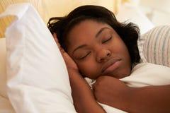 Überladene Frau schlafend im Bett Lizenzfreies Stockfoto
