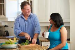 Überladene Paare auf der Diät, die Gemüse in der Küche vorbereitet Stockfotografie