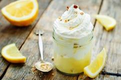 Überlagerter Nachtisch mit Zitronencreme, Eiscreme und Schlagsahne Stockfotografie