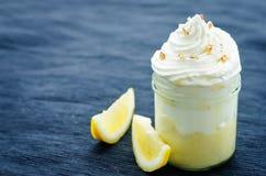 Überlagerter Nachtisch mit Zitronencreme, Eiscreme und Schlagsahne Lizenzfreie Stockfotos