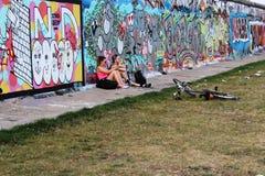 Berlijn, Duitsland, 2014: Een kerel en een meisje zitten dichtbij de muur met graffiti Stock Foto's