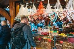 Berlijn, 03 Oktober, 2017: Het vieren van de man van Oktoberfest A naast de teller bekijkt divers traditioneel suikergoed Stock Afbeelding