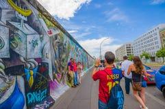 BERLIM, ALEMANHA - 6 DE JUNHO DE 2015: Turists que toma fotografias no muro de Berlim dos grafittis, maneiras de expressar theirs Fotos de Stock