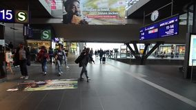 Berlim, Alemanha, o 8 de maio de 2019: Passageiros no estação de caminhos de ferro Grupo de pessoas com sua bagagem que anda no t vídeos de arquivo