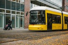 Berlim, o 12 de dezembro de 2017: Um bonde amarelo moderno tradicional que abaixa a rua da cidade Um pai com uma criança pequena Fotografia de Stock