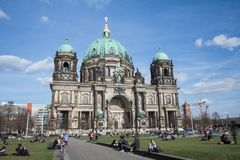 The Berlin Cathedral in German, `Berliner Dom`, designed by Julius Carl Raschdorff. People enjoying the warm afternoon in the Lu. Stgarten stock photography