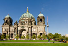 Berlin Cathedral. Tourists on the lawn in front of the Berlin cathedral, with the TV tower behind it Royalty Free Stock Photos