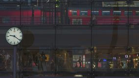 Berlin Central Station Train Departing. Berlin Central Railway Station At Night. Frontal Glass Facade With Clock. People Walking And Red Regional Train Departing stock video footage