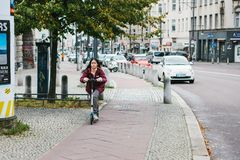 Berlin, December 12, 2017: A girl on a scooter rides a special bike path along the city street next to the buildings stock photos