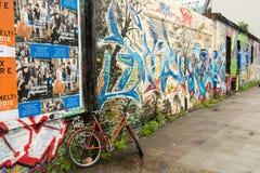 BERLIN/DEUTSCHLAND - CIRCA im September 2012 - ein Fahrrad wird gegen einen Pfosten nahe bei einer Wand gebunden, die mit Graffit Lizenzfreies Stockbild