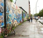 BERLIN/DEUTSCHLAND - CIRCA im September 2012 - ein Fahrrad wird gegen einen Pfosten nahe bei einer Wand gebunden, die mit Graffit Stockfotos