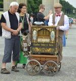 Berlin, Deutschland - Juli 2015 - Drehorgelspieler mit älteren touristischen Paaren Lizenzfreies Stockfoto