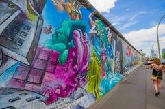 BERLIN, DEUTSCHLAND - 6. JUNI 2015: Graffiti-Berliner Mauer auf der Mitte der Stadtmenschen, die herum gehen Stockfoto