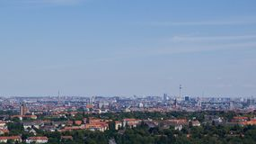 Berlin distant skyline. Berlin skyline with television tower in distance and green foliage in foreground under clear blue sky Royalty Free Stock Photos