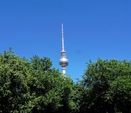 Berlin Fernsehturm in front of blue sky. Berlin television tower behind trees and in front of blue sky Stock Images