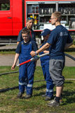 Berlin firefighter shows a group of children skills of working with fog nozzle. BERLIN - JUNE 11, 2016: Berlin firefighter shows a group of children skills of royalty free stock images