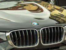 BMW emblem on a shiny black car. Berlin, Germany - April 25, 2018: Bmw motor company emblem on the front of a car. BMW Bayerische Motoren Werke is a German stock images
